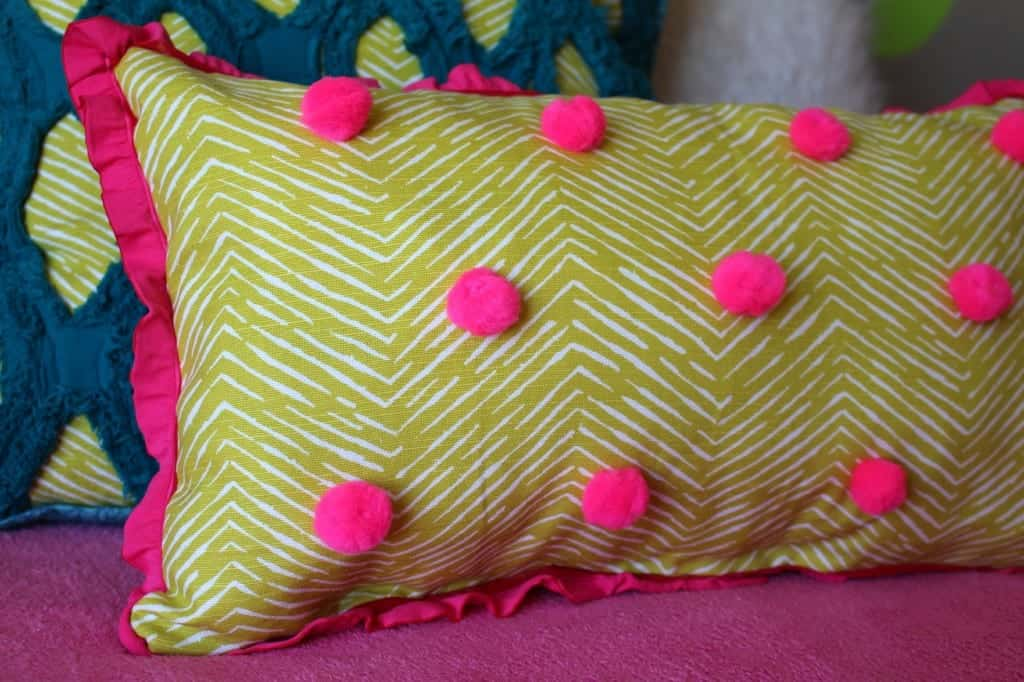 close up of polka dot pom pom pillow a girl and a glue gun